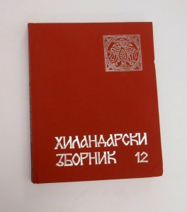 A photograph of volume 12 of the journal Hilandarski zbornik: the book has a red cloth cover with Serbian Cyrillic name of the journal in silver followed by the numeral 12 at the bottom of the front cover and a silver square seal of the two-headed eagle in the upper right corner of the book.