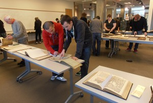 Photograph of patrons examining printed books that are displayed on long tables