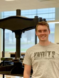 A photo of Alec Reynolds standing in front of a piece of antique machinery at the Library Tech Center.