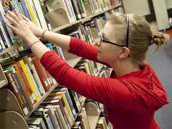 Student reaching for books on a shelf