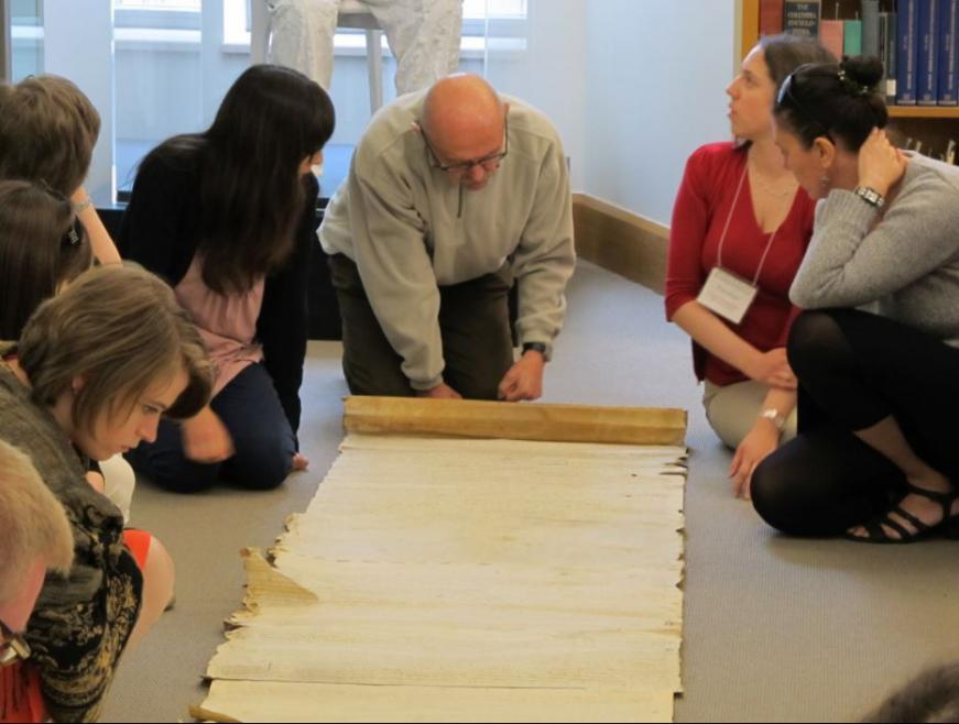 Summer institute participants examine a scroll.