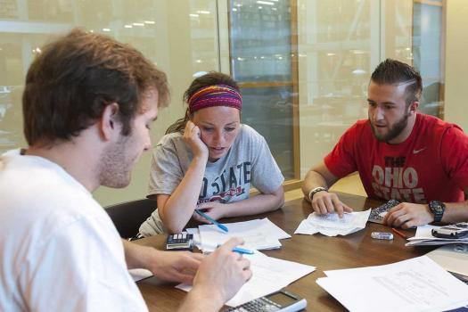 Three students in a Thompson Library group study room.