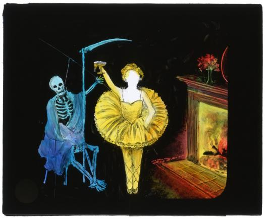 Painted glass slide with skeleton death figure with sickle sitting next to ballerina in tutu