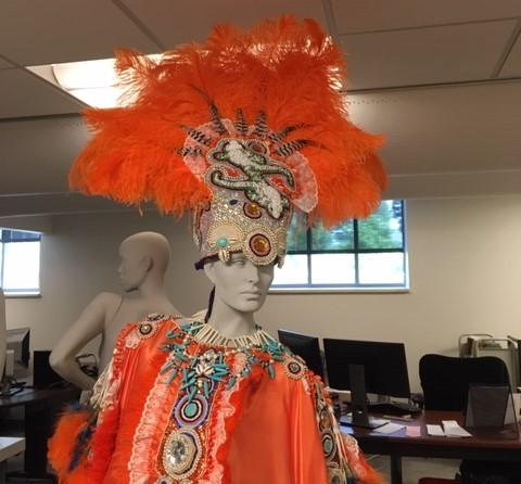 mannequin dressed in bright red costume with red feathered headdress