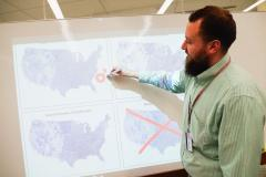 Josh Sadvari stands in front of a whiteboard showing a projection of several maps of the United States. He is using a red marker to annotate the maps.