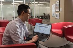 Lee-Arng Chang sits in a red chair in the Research Commons lobby. He is holding a laptop which is displaying multiple graphs and charts on a dashboard.