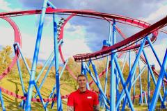 Alec Reynolds, wearing a red polo shirt, stands in front of a large red and blue roller coaster.