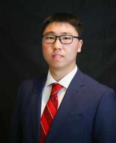 A professional portrait of Zhiren Xu. He is wearing a navy blue suit and a red tie and is seated in front of a black background.