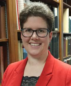Tamar Chute stands in front of a full bookcase. She has short, dark hair and is wearing glasses and a red blazer. She is smiling.