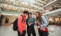 Two students stand next to a faculty member, looking at something on her iPad in front of the Thompson Library book stacks.