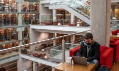 A student sits in a red chair in front of the stacks at Thompson Library, studying something on his laptop.